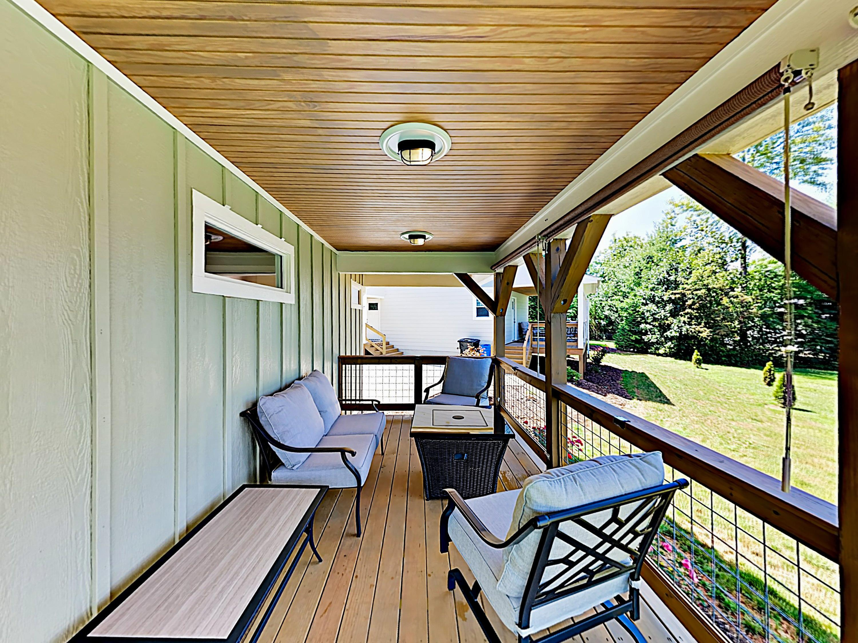 The covered back deck is equipped with cushioned seating for 4 and a gas fire pit.