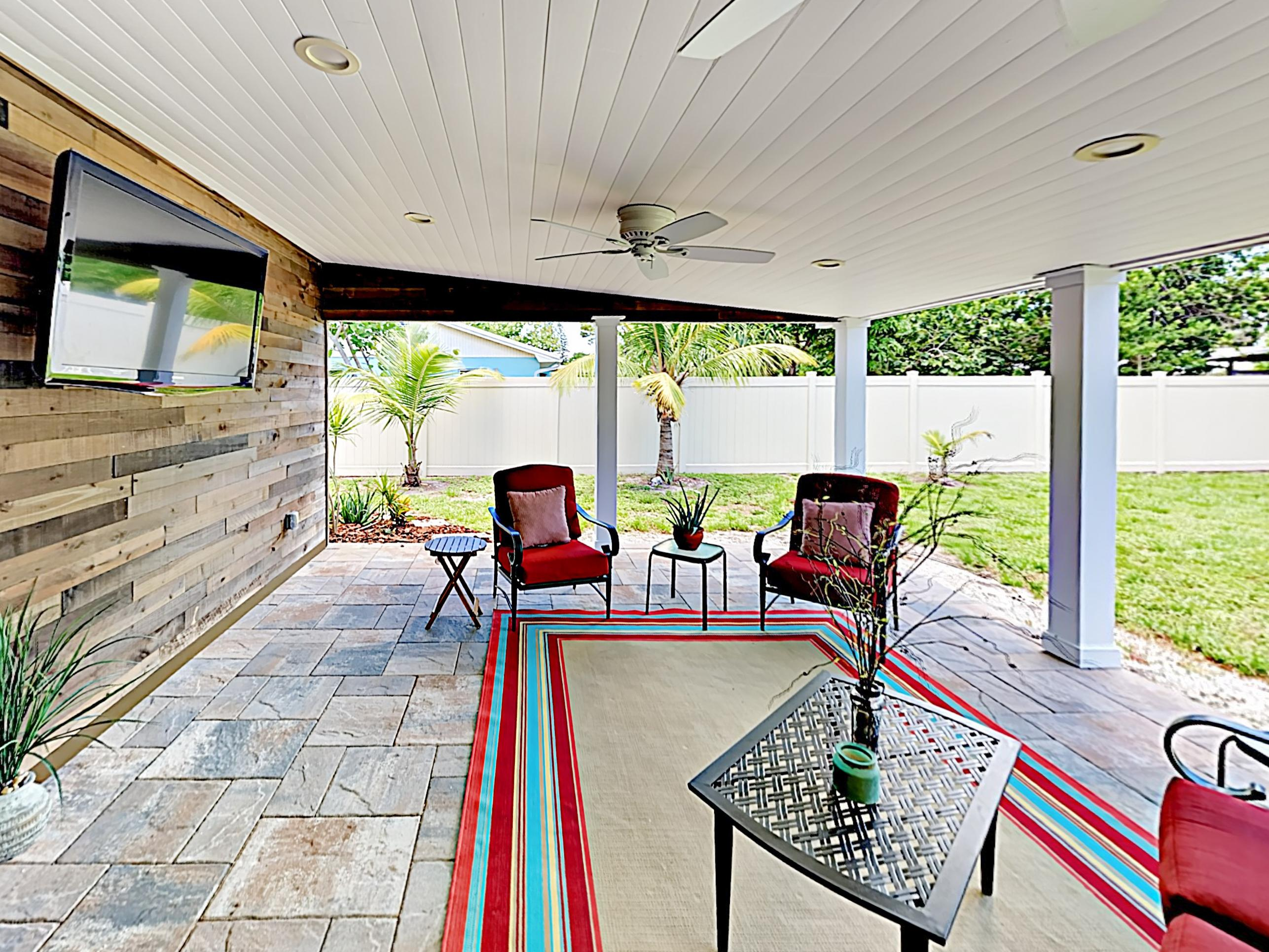 "Kick back on the covered patio, where comfy furniture and a 55"" smart TV create an inviting outdoor living area."