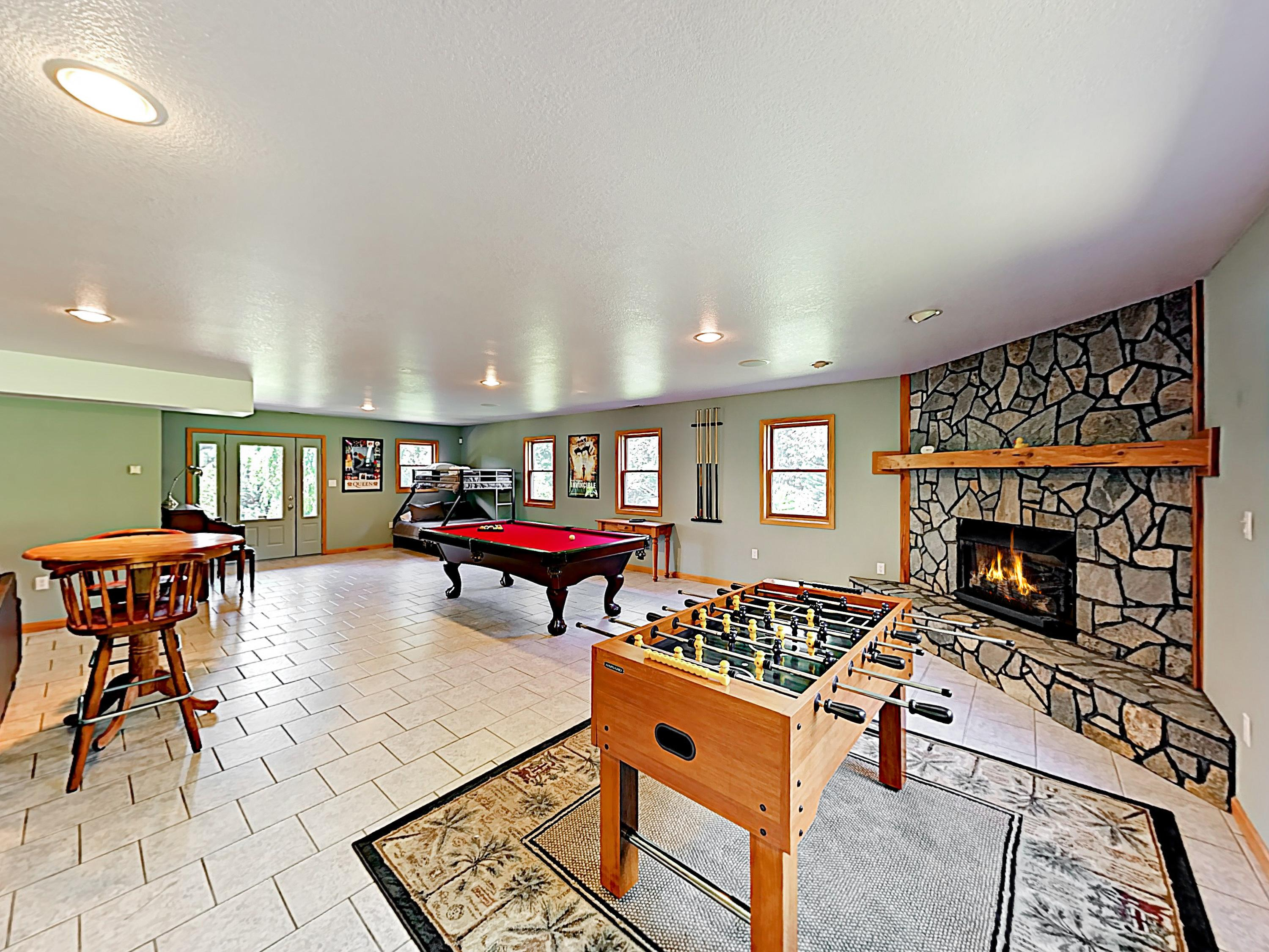 A gas fireplace adds ambience to the spacious game room, detailed with foosball, billiards, and a card table.