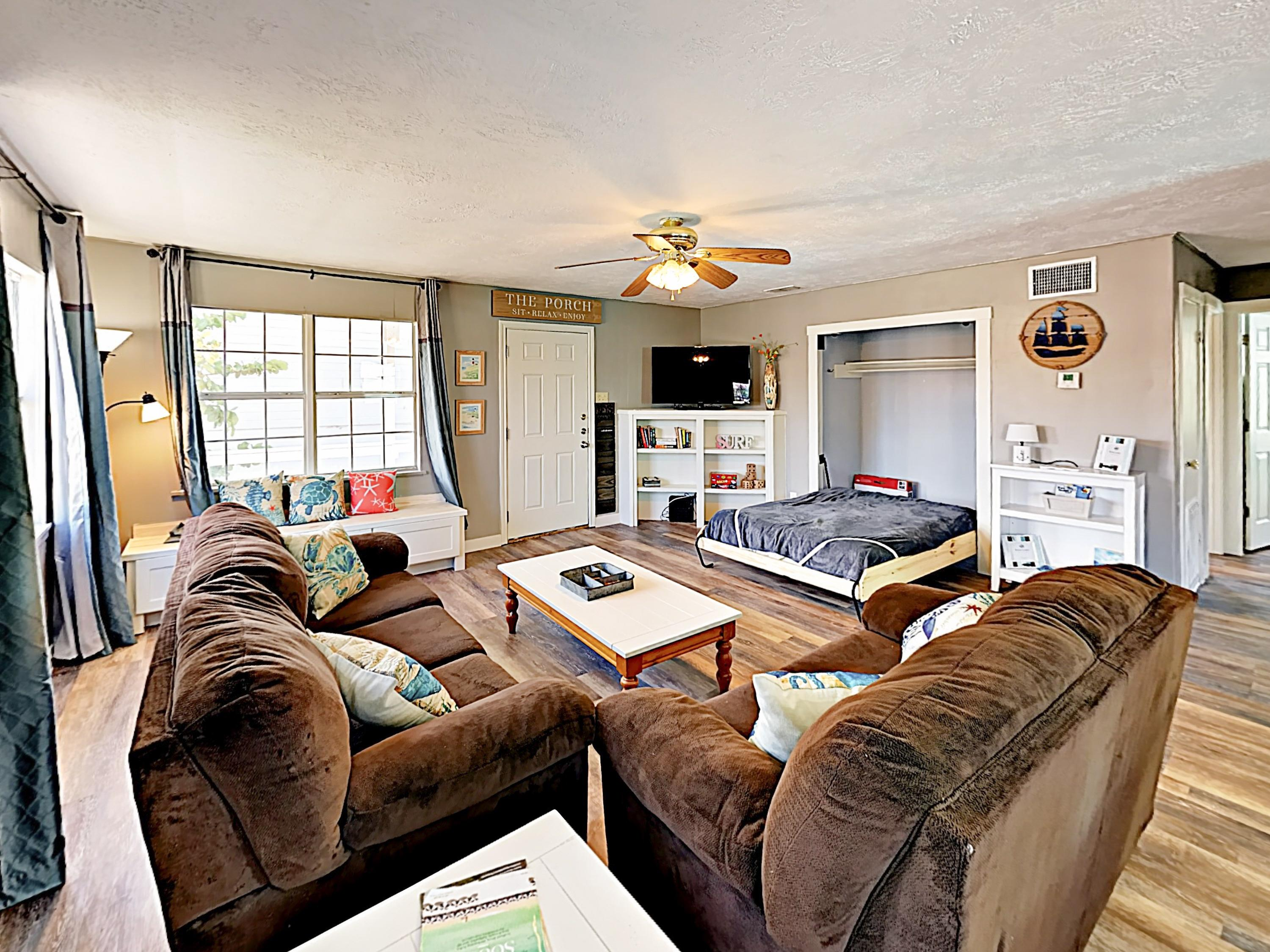 "Relax in the open living area, furnished with a plush sofa, love seat, Murphy bed, and 50"" TV."