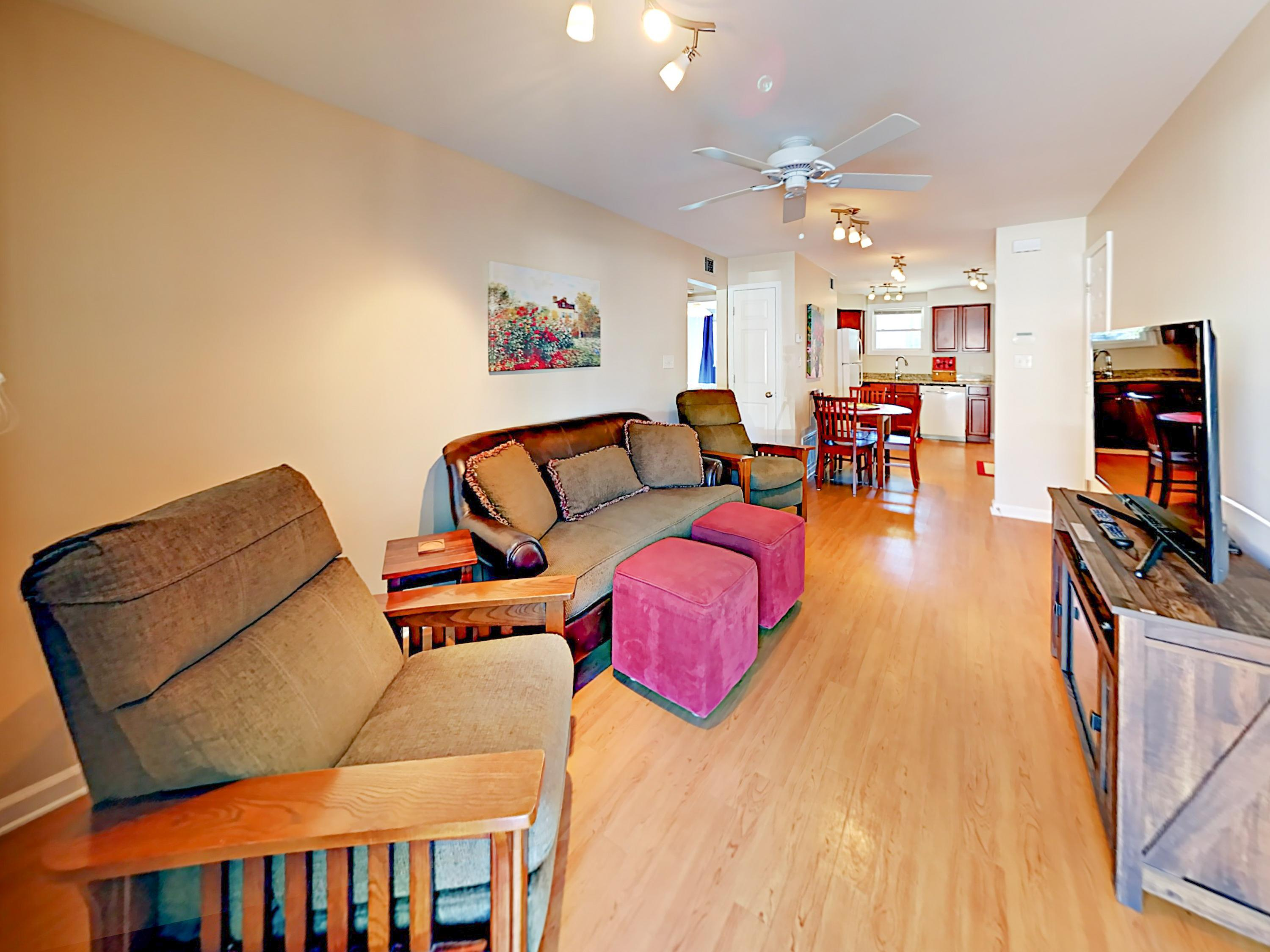 "The cozy living area in Unit 1 offers a couch, 2 armchairs, and a 50"" TV."