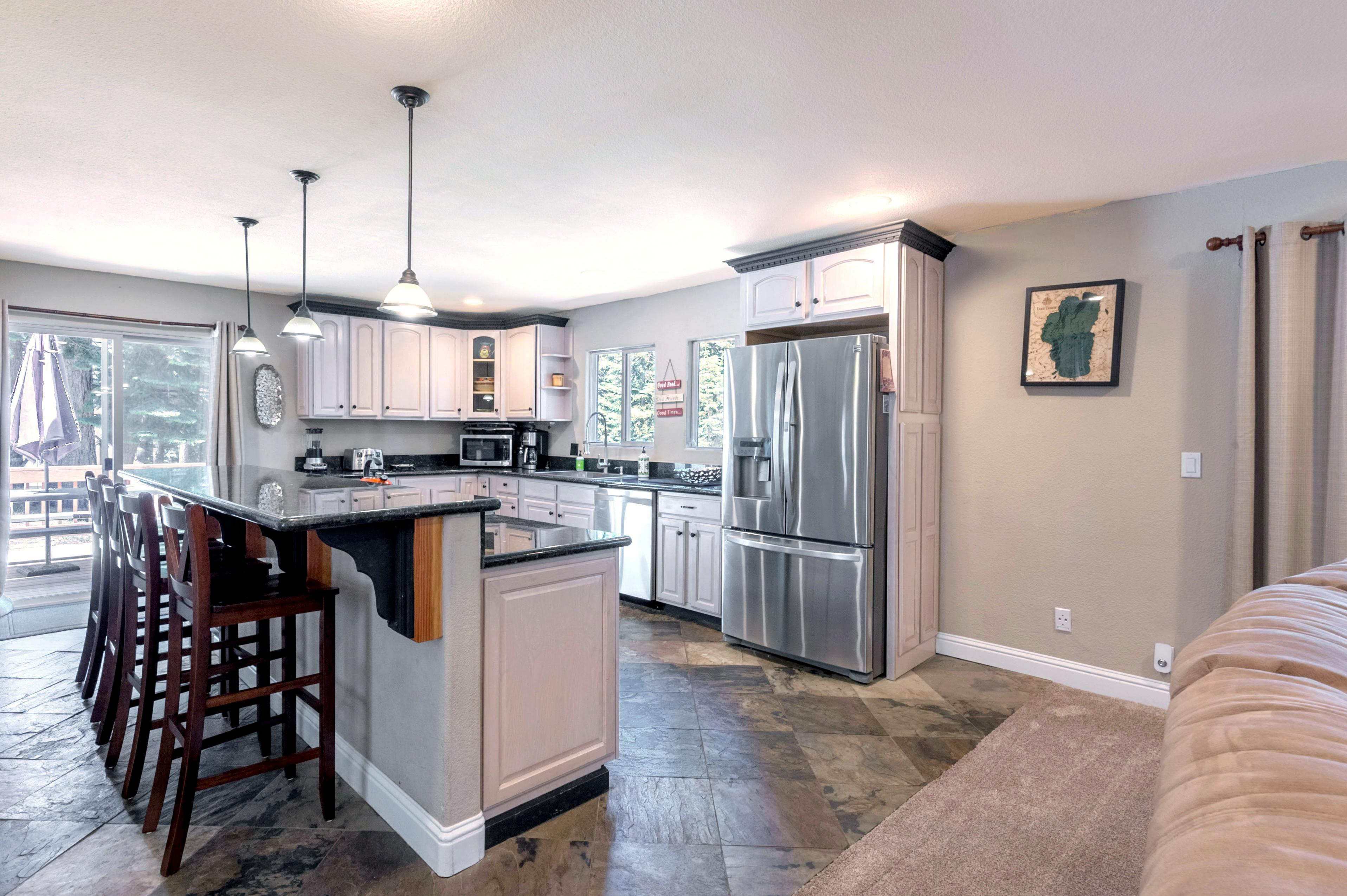 The sunny kitchen is outfitted with a full suite of stainless steel appliances and granite countertops.