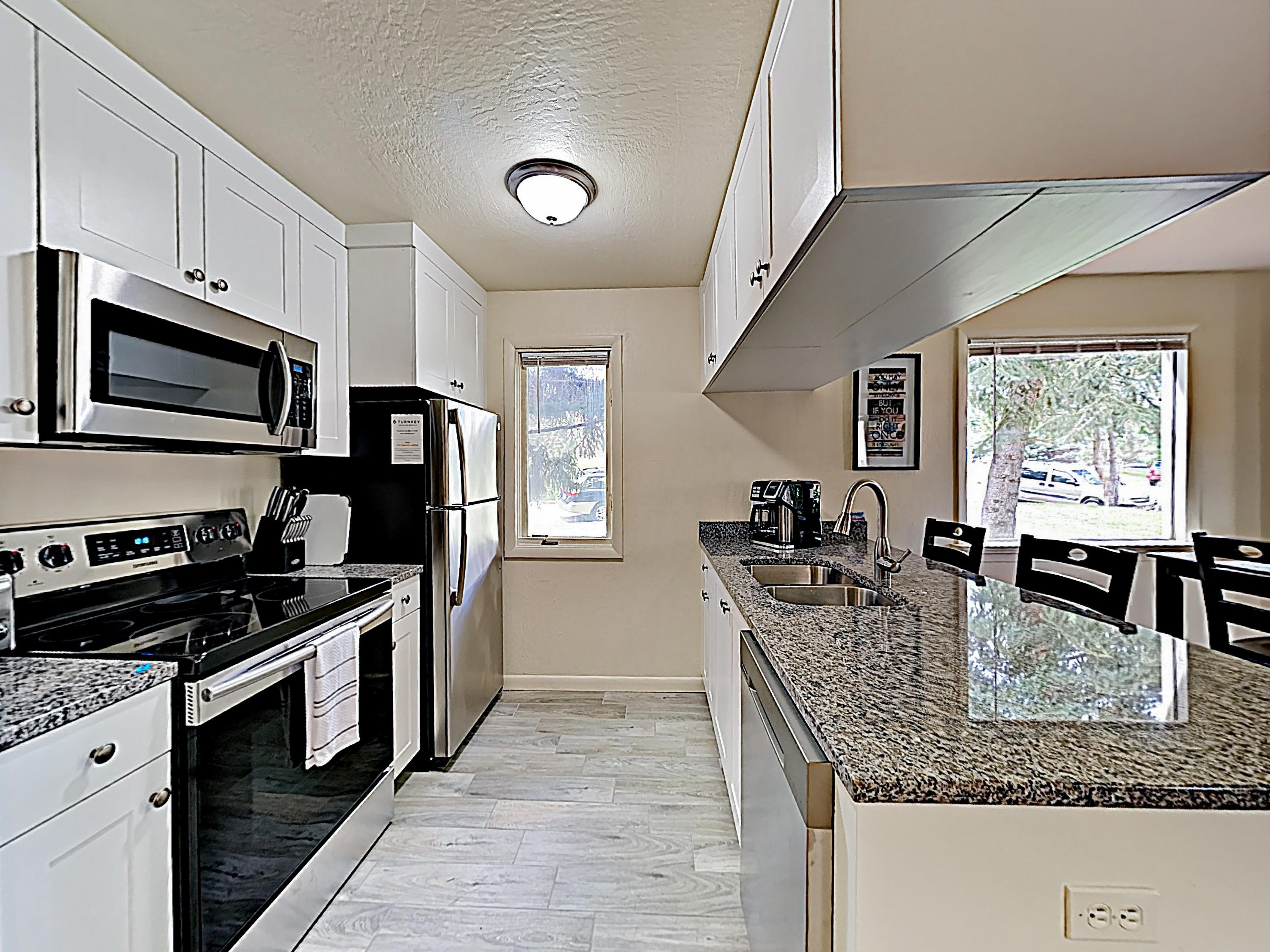 Whip up hearty meals in the kitchen, outfitted with granite countertops, white cabinetry, and stainless steel appliances.