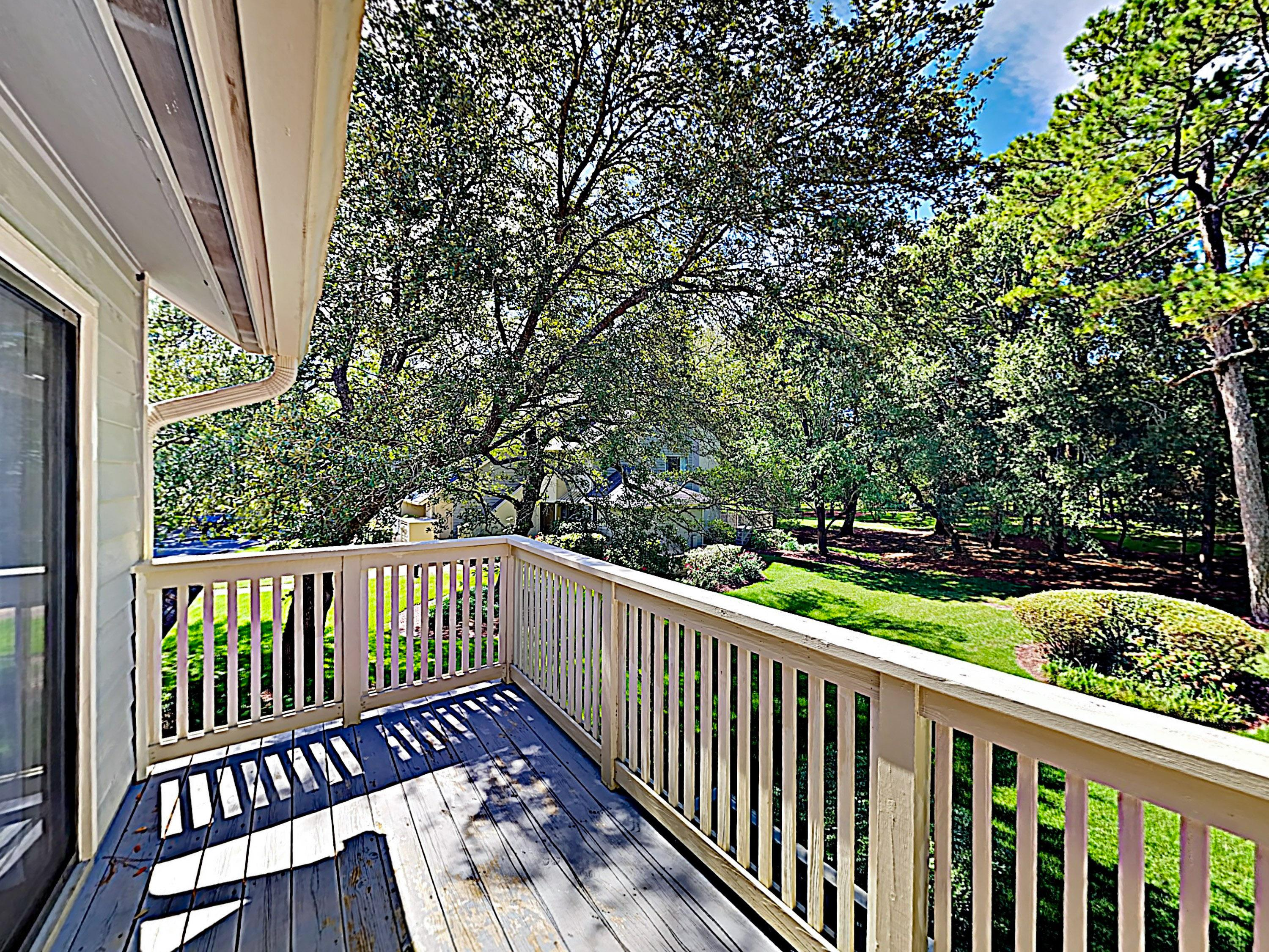 A private balcony provides greenery views of the wooded backyard.