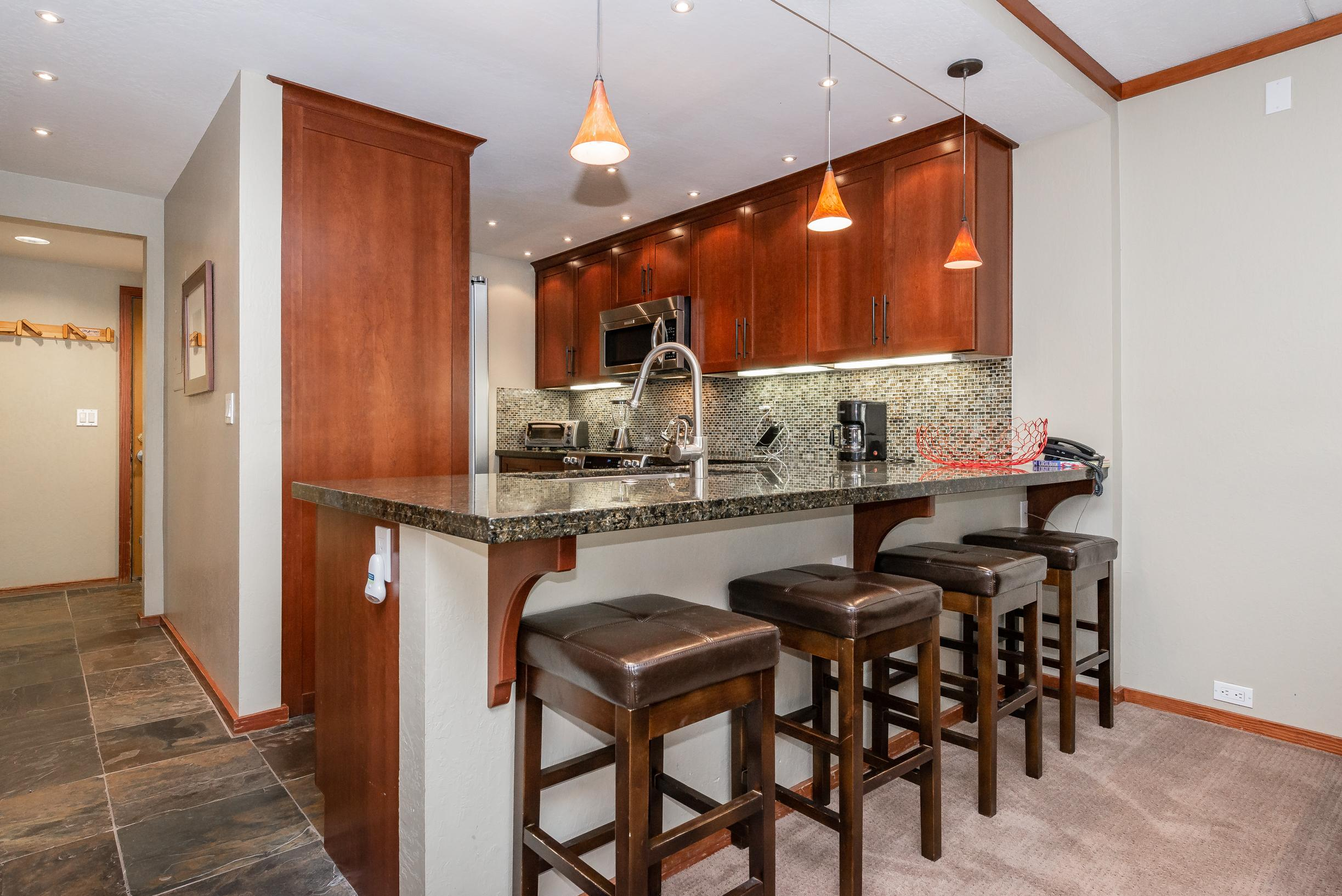 Cherry wood cabinetry and granite countertops outfit the well-equipped kitchen. Keep the chef company at the kitchen bar with seating for 4.
