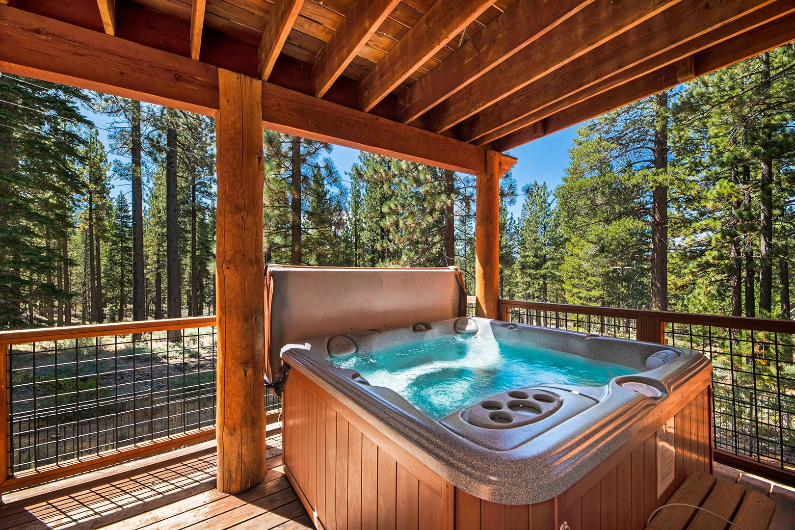 Enjoy wooded views while soaking in the private hot tub.