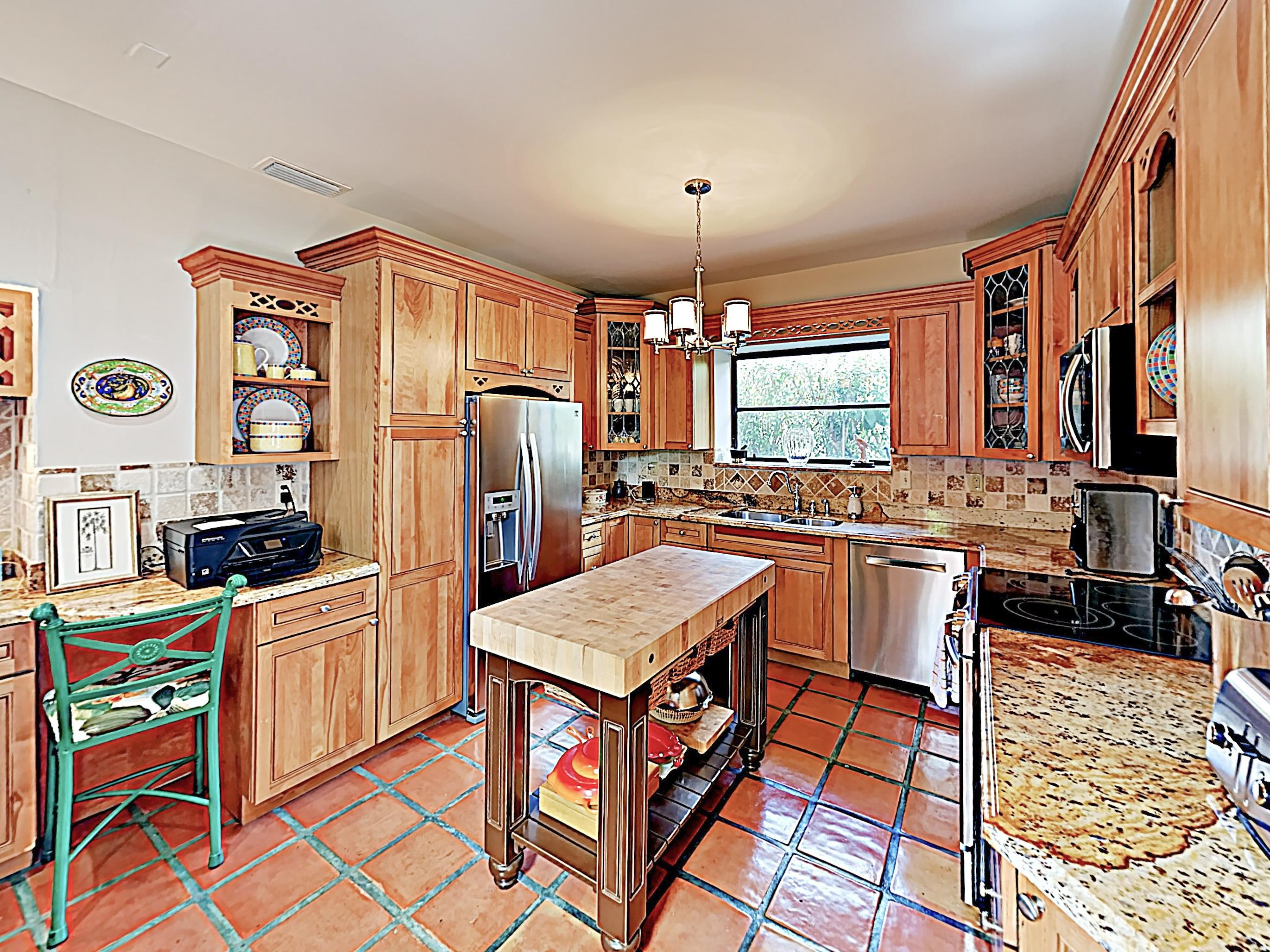 The freshly renovated kitchen boasts gleaming granite countertops and a full suite of stainless steel appliances.