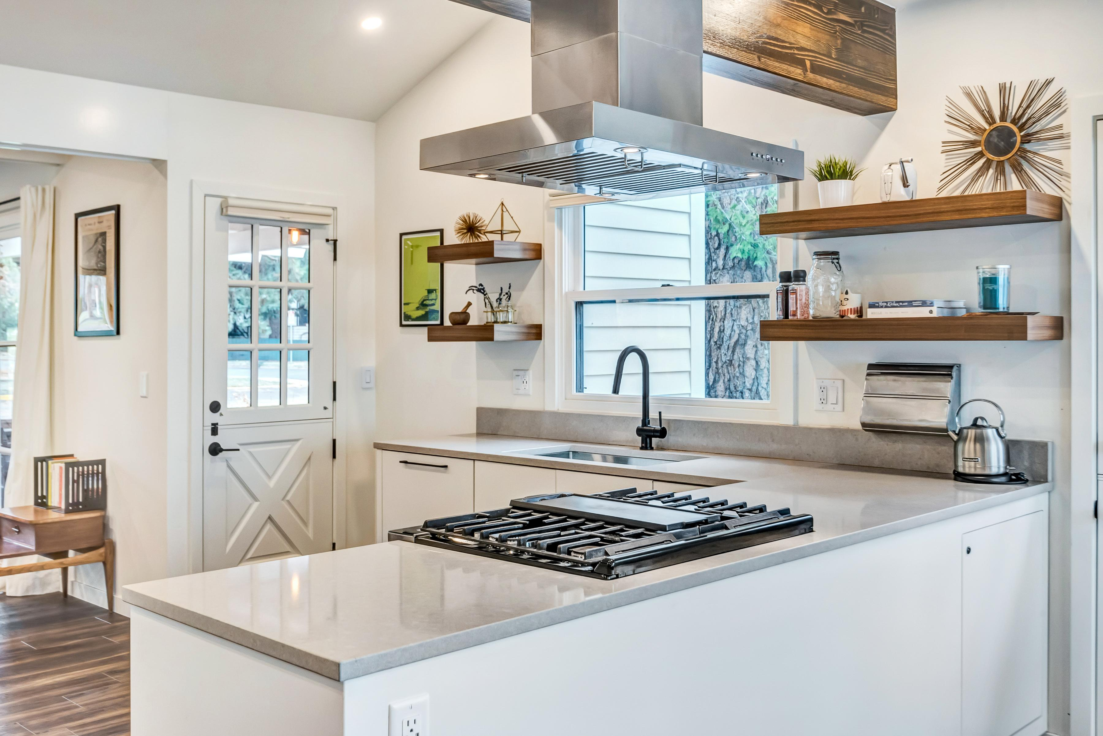 The sleek kitchen is outfitted with quality stainless steel appliances and granite countertops.