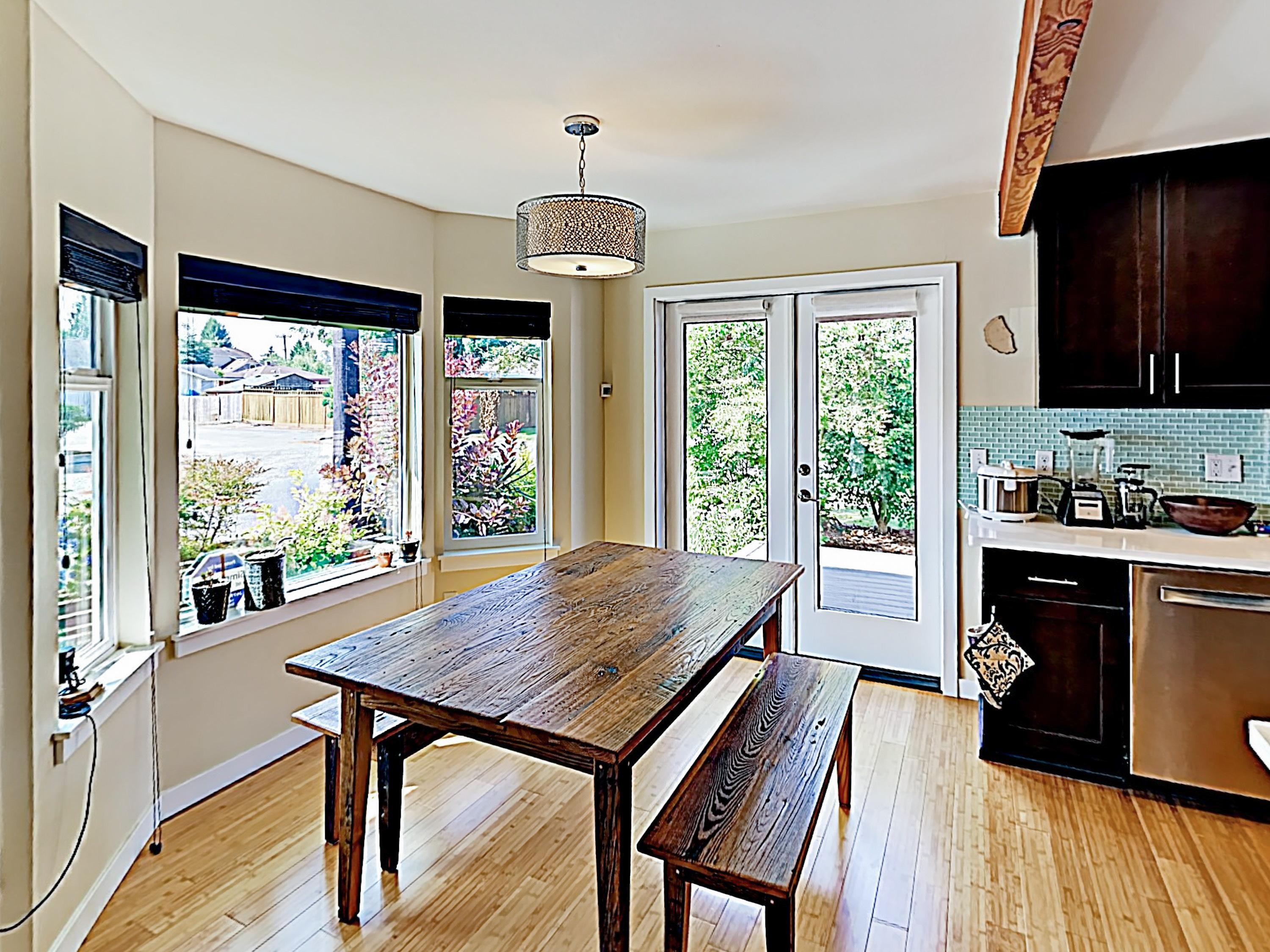 The dining area features a wood table and a large bay window.