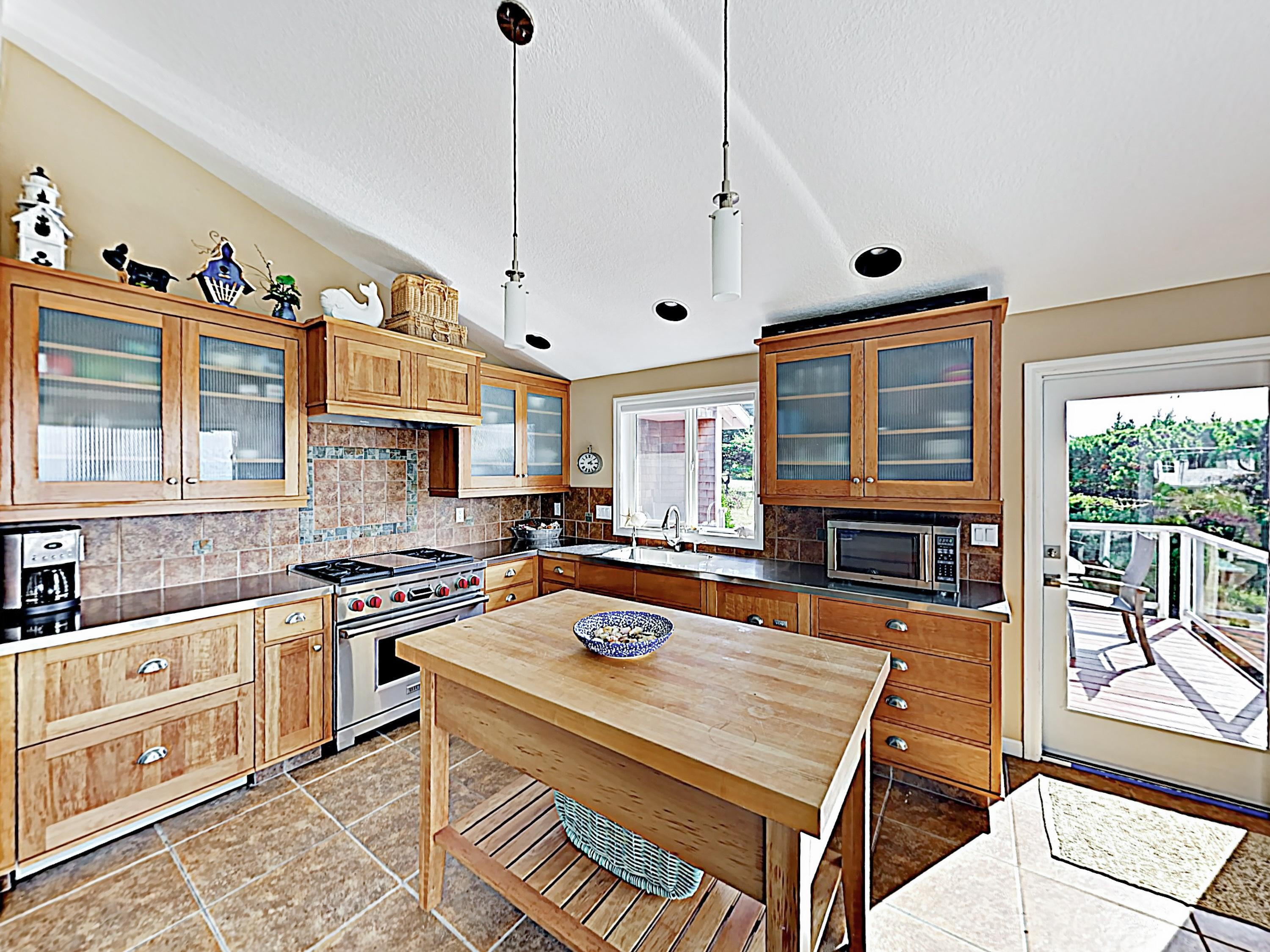 The sparkling kitchen provides stainless steel appliances, including a Wolf range and oven.