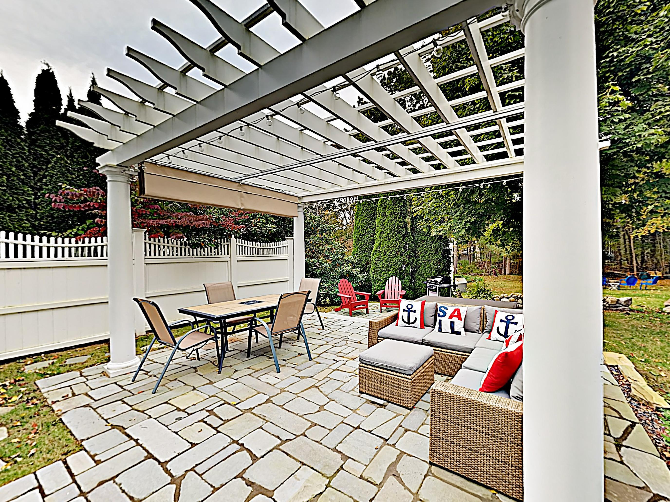 A lovely pergola on the stone patio sets the scene for relaxing in the great outdoors.