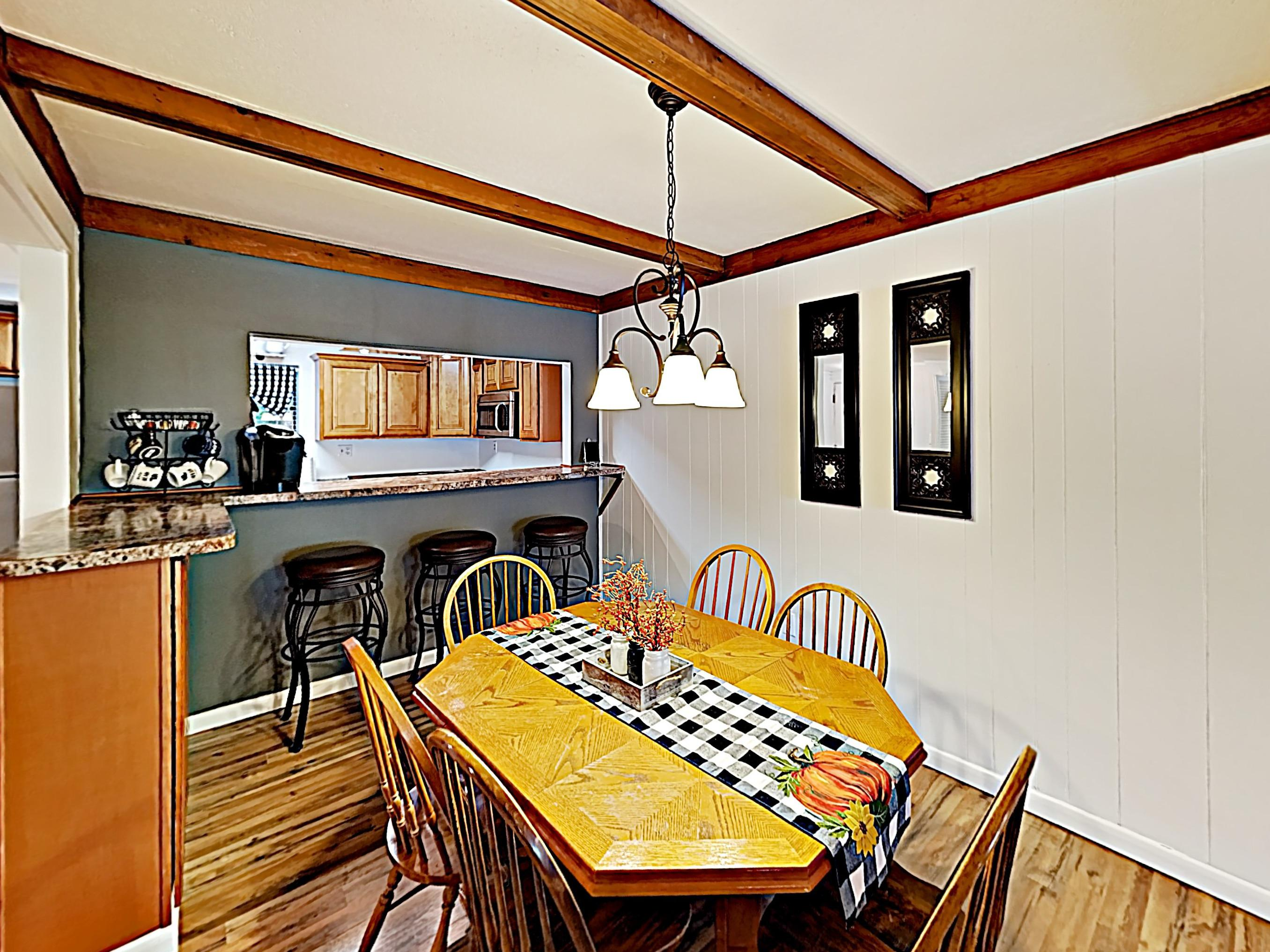 Enjoy home-cooked vacation meals together at the wooden dining table, set for 6.