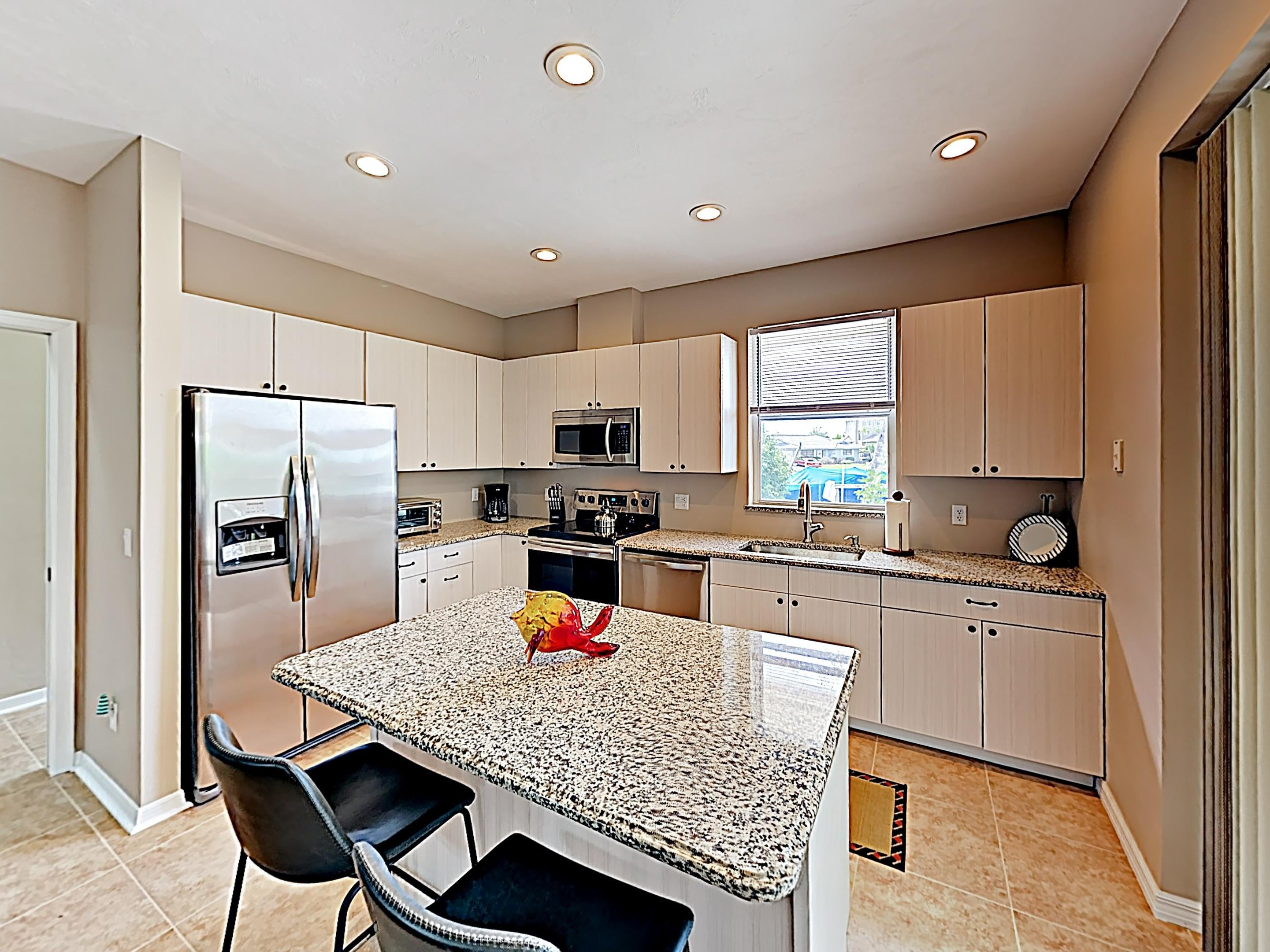 A contemporary kitchen includes a 2-person breakfast bar.