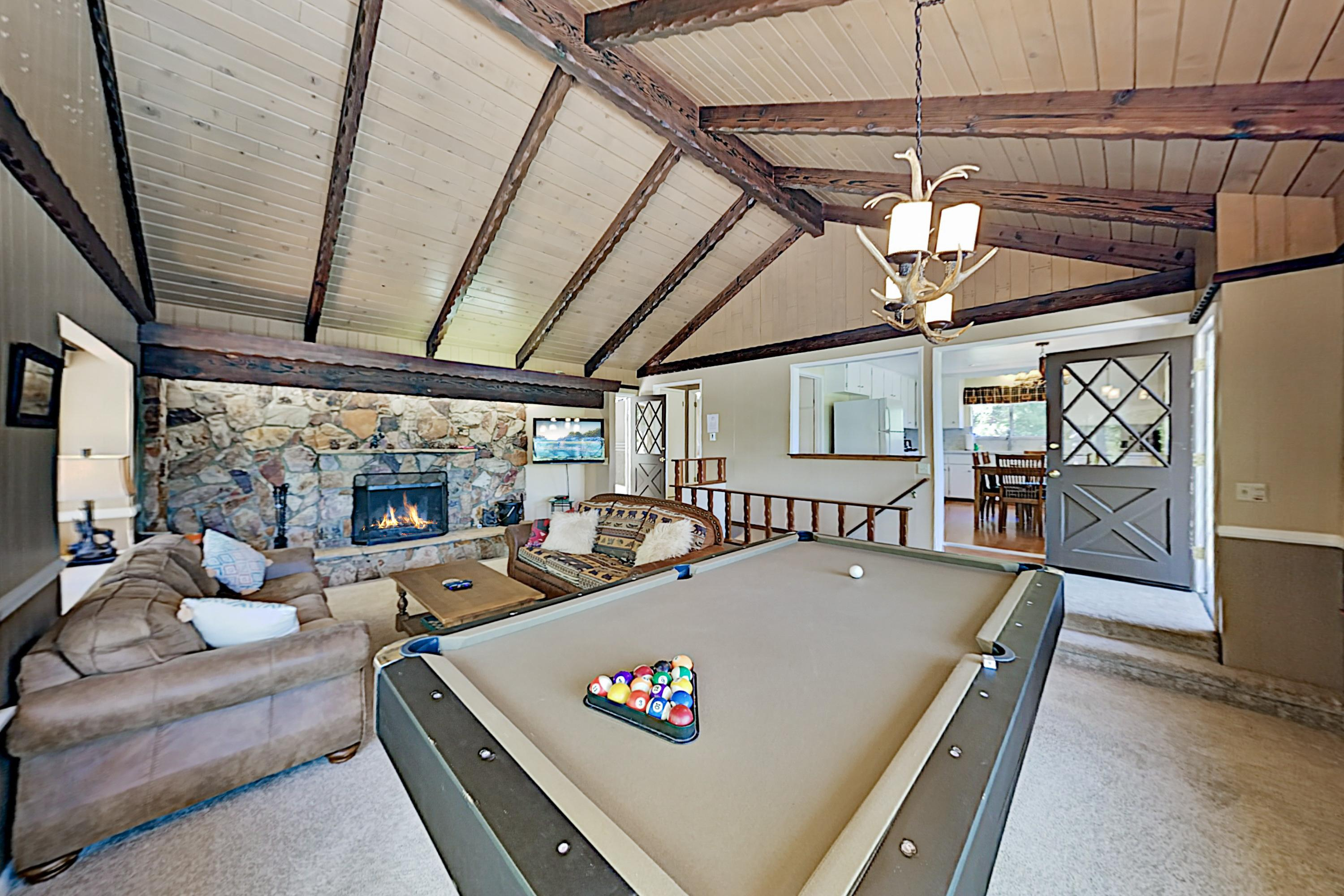 A gorgeous pool table sits beneath vaulted ceilings in the living room.