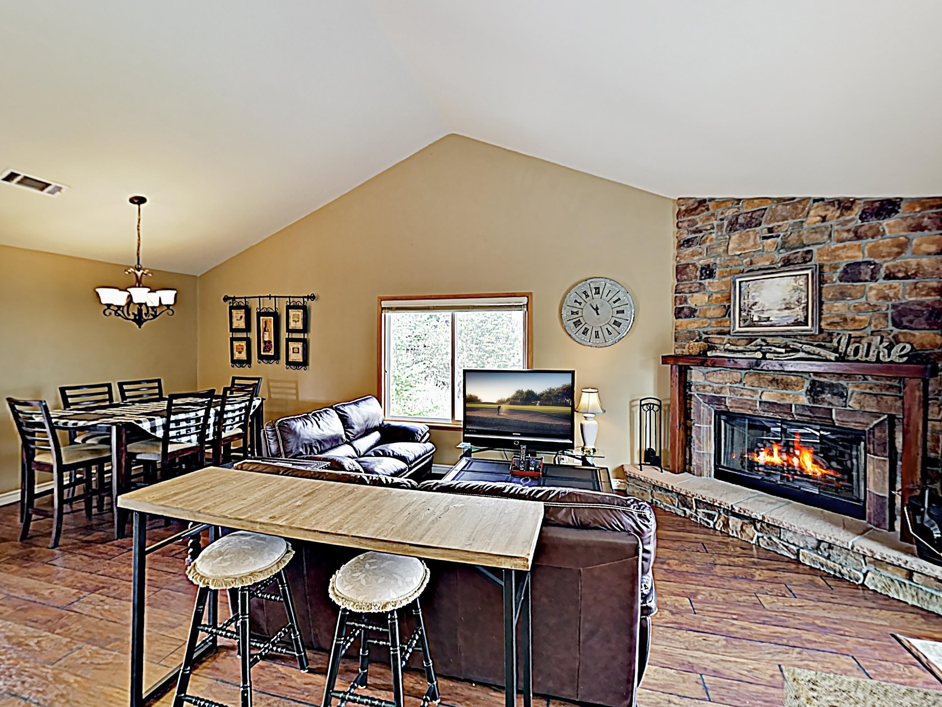 Vaulted ceilings soar in the open-concept living room. A wood-burning fireplace sits center stage.