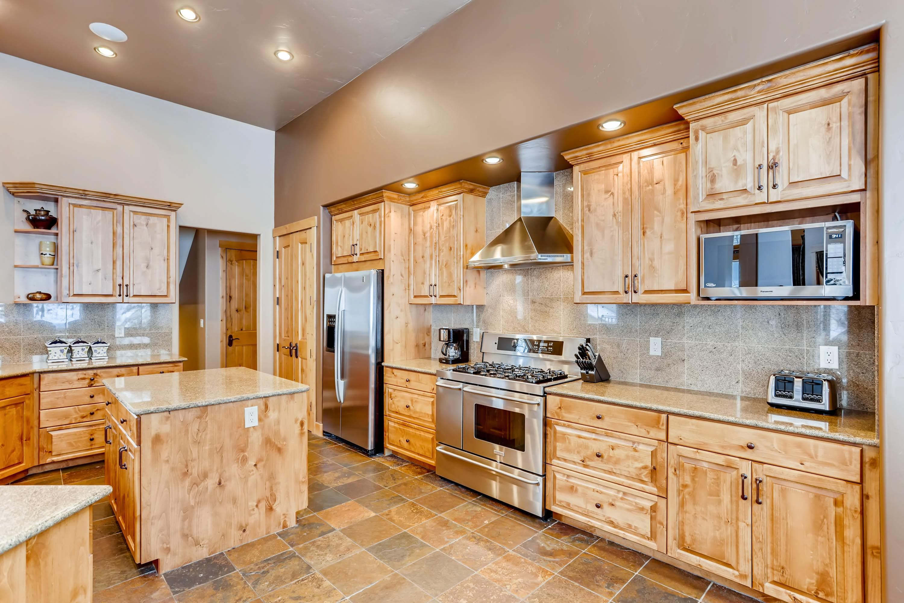 Granite countertops and stainless steel appliances complement warm wood cabinetry in the chef's kitchen.