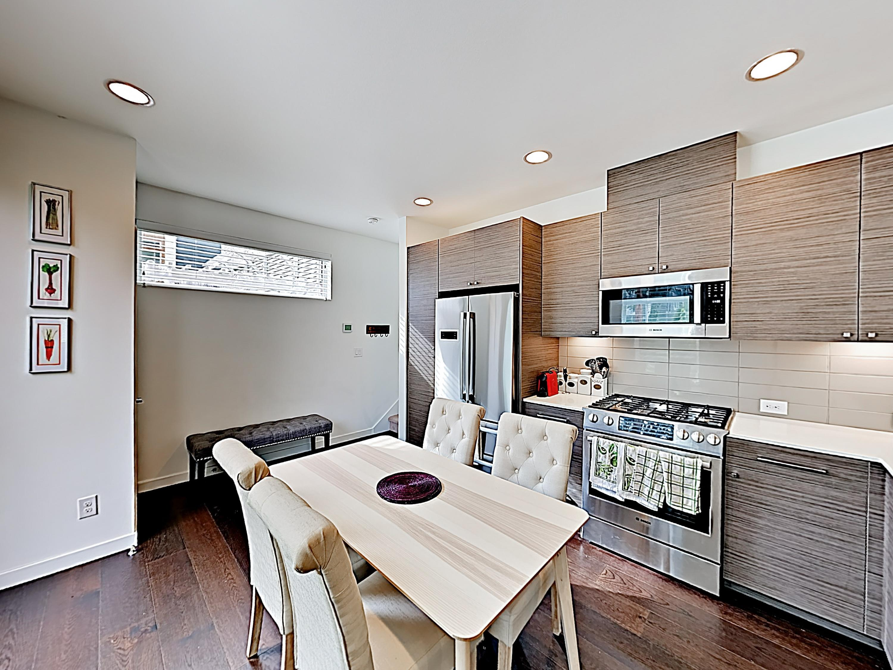 The modern kitchen is equipped with a full suite of stainless steel appliances.