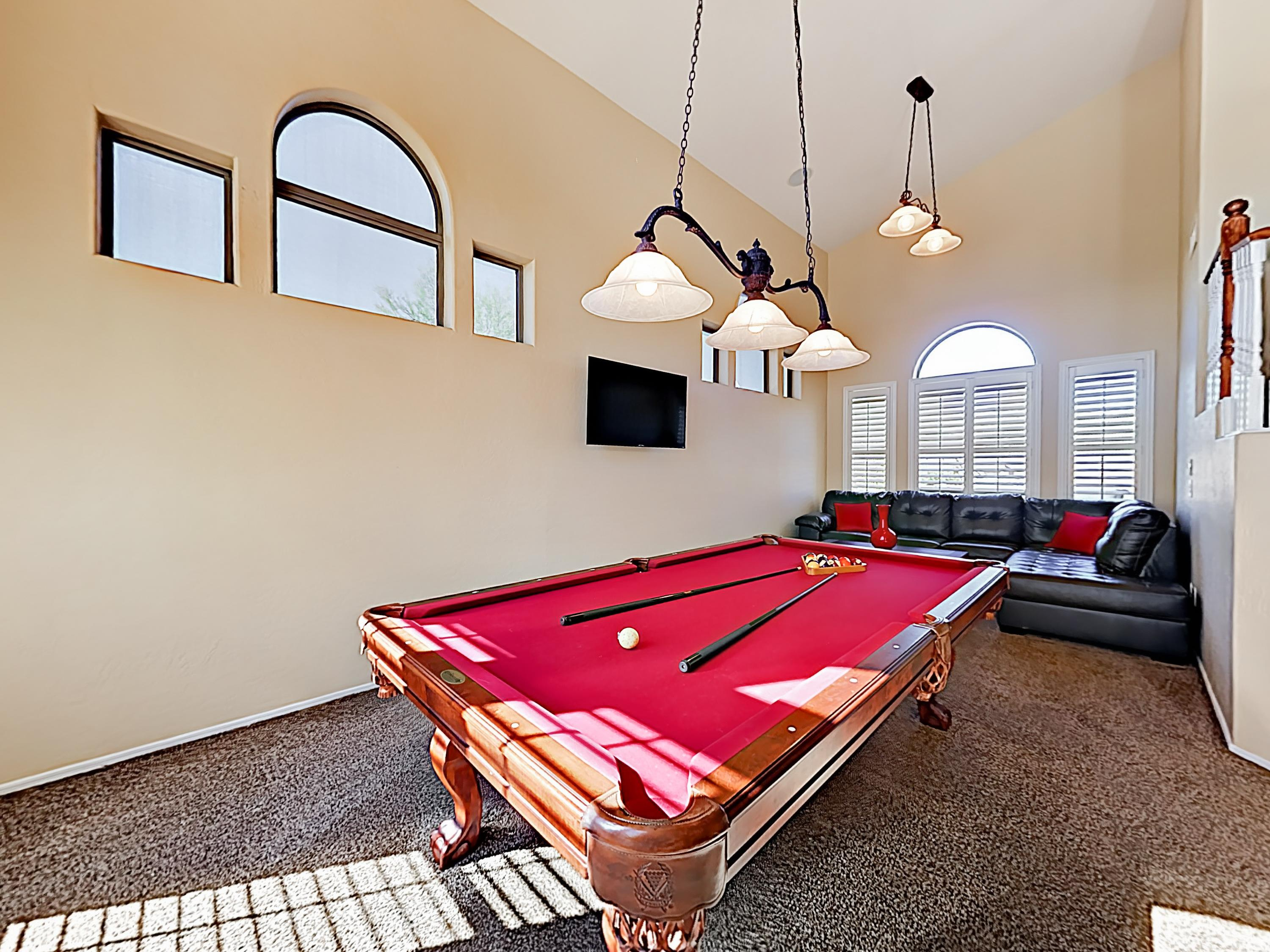 "The downstairs game room boasts a pool table,  stylish sectional, and 50"" wall-mounted TV."