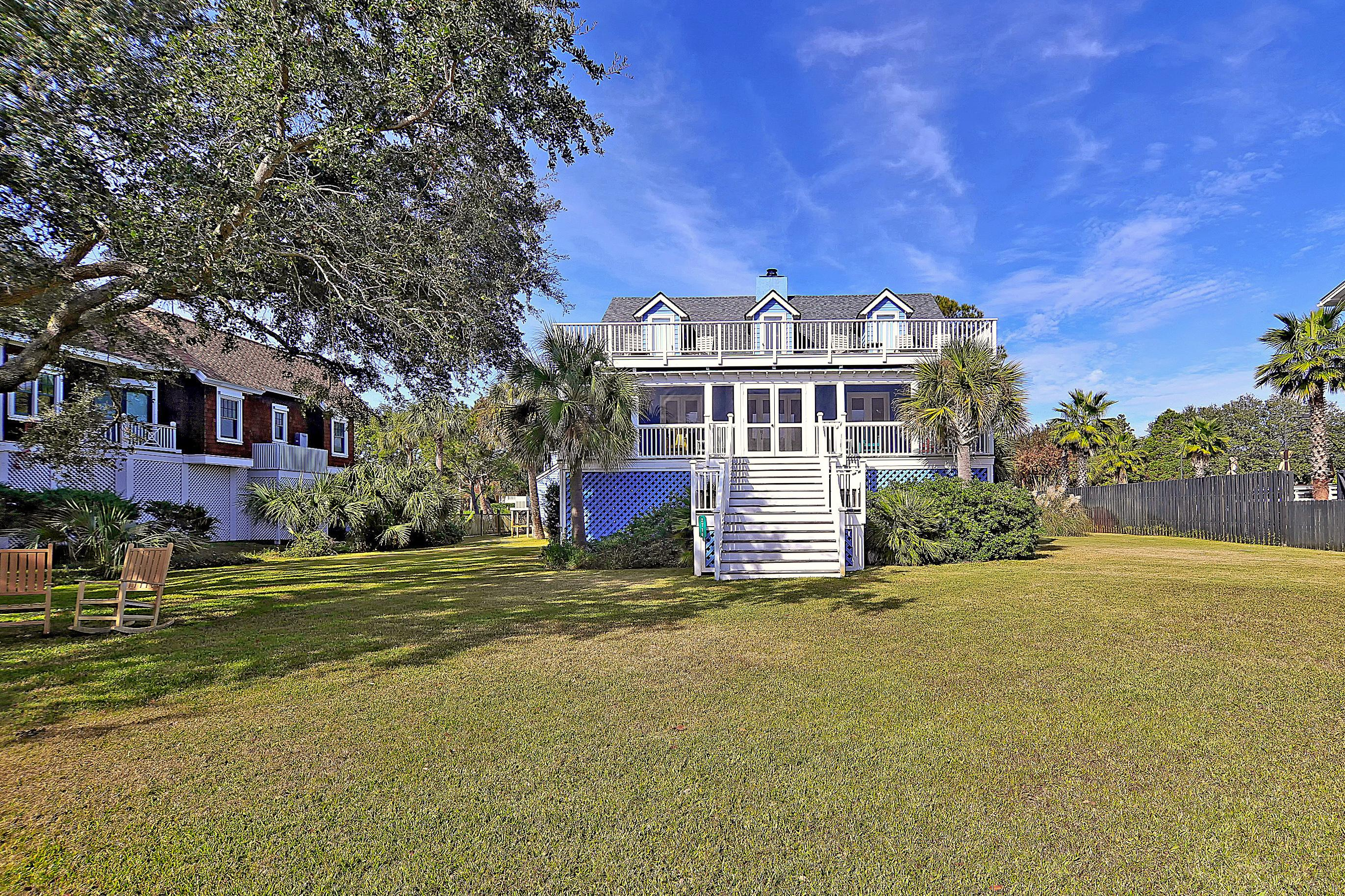 Welcome to Sullivan's Island! A balcony, sun deck, and a sprawling porch overlook the lush yard.