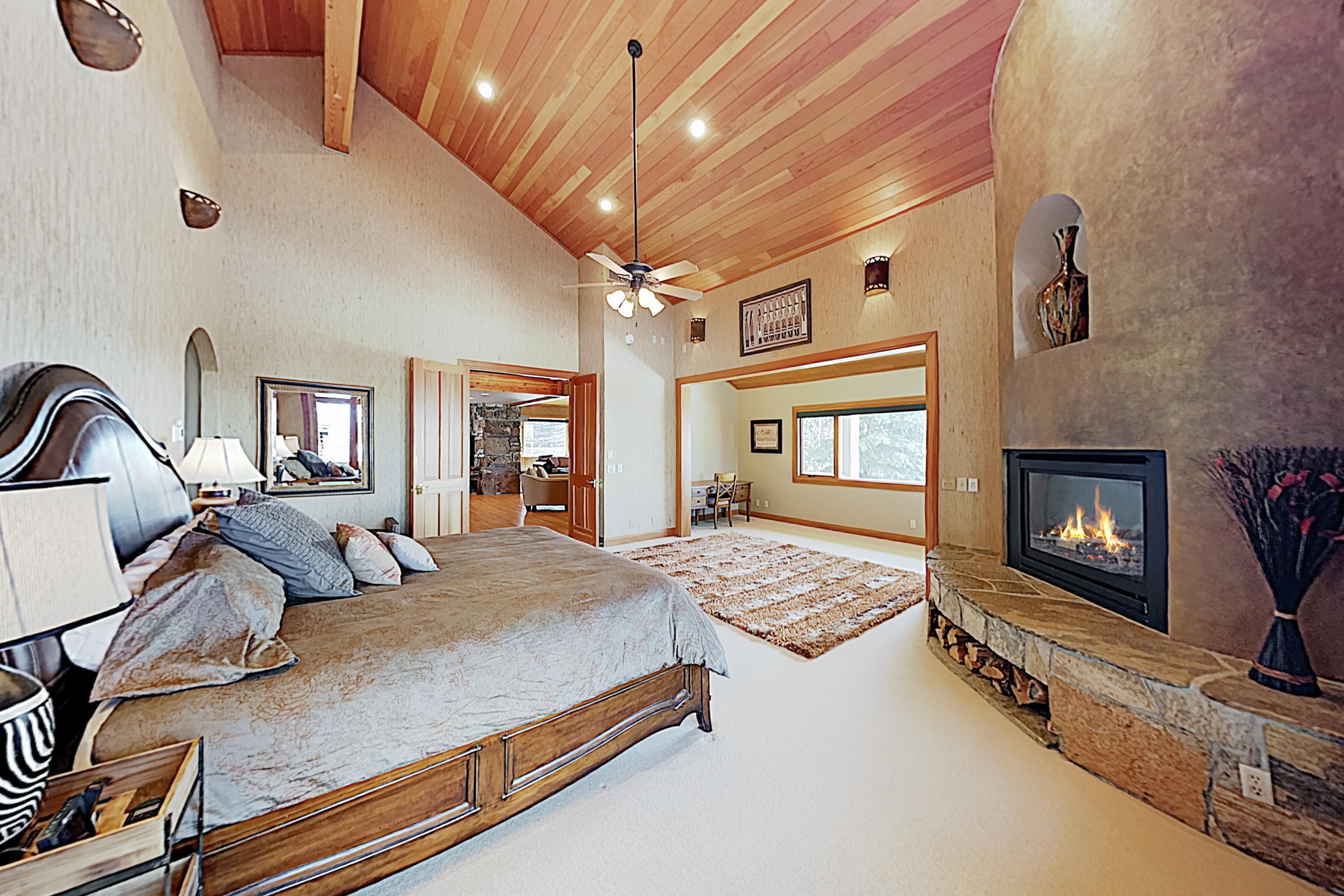 The stately master bedroom has a king bed and a gas fireplace.
