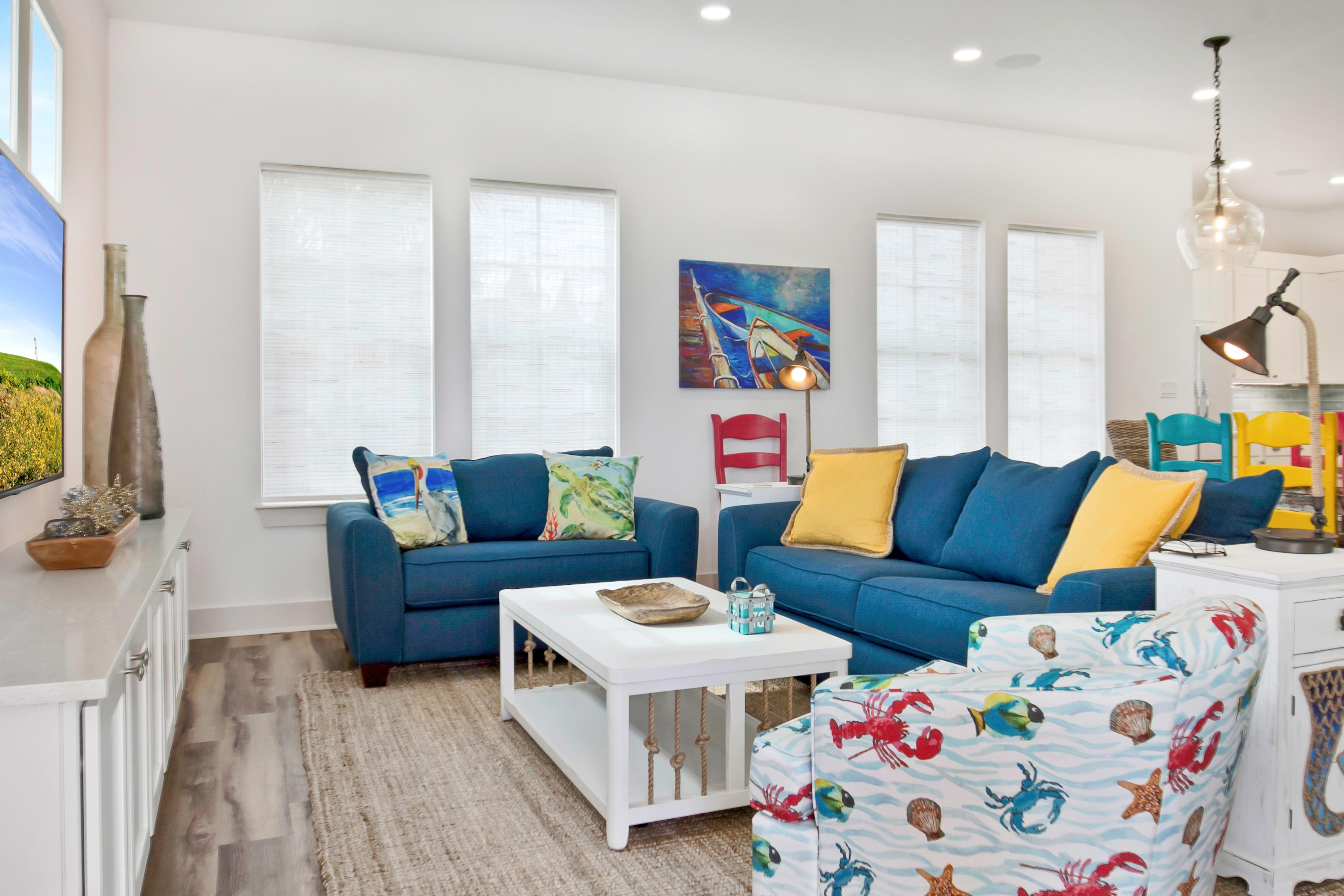 The sunny main living area is furnished with a sofa, an oversized chair for 2, and a plush rocking chair.