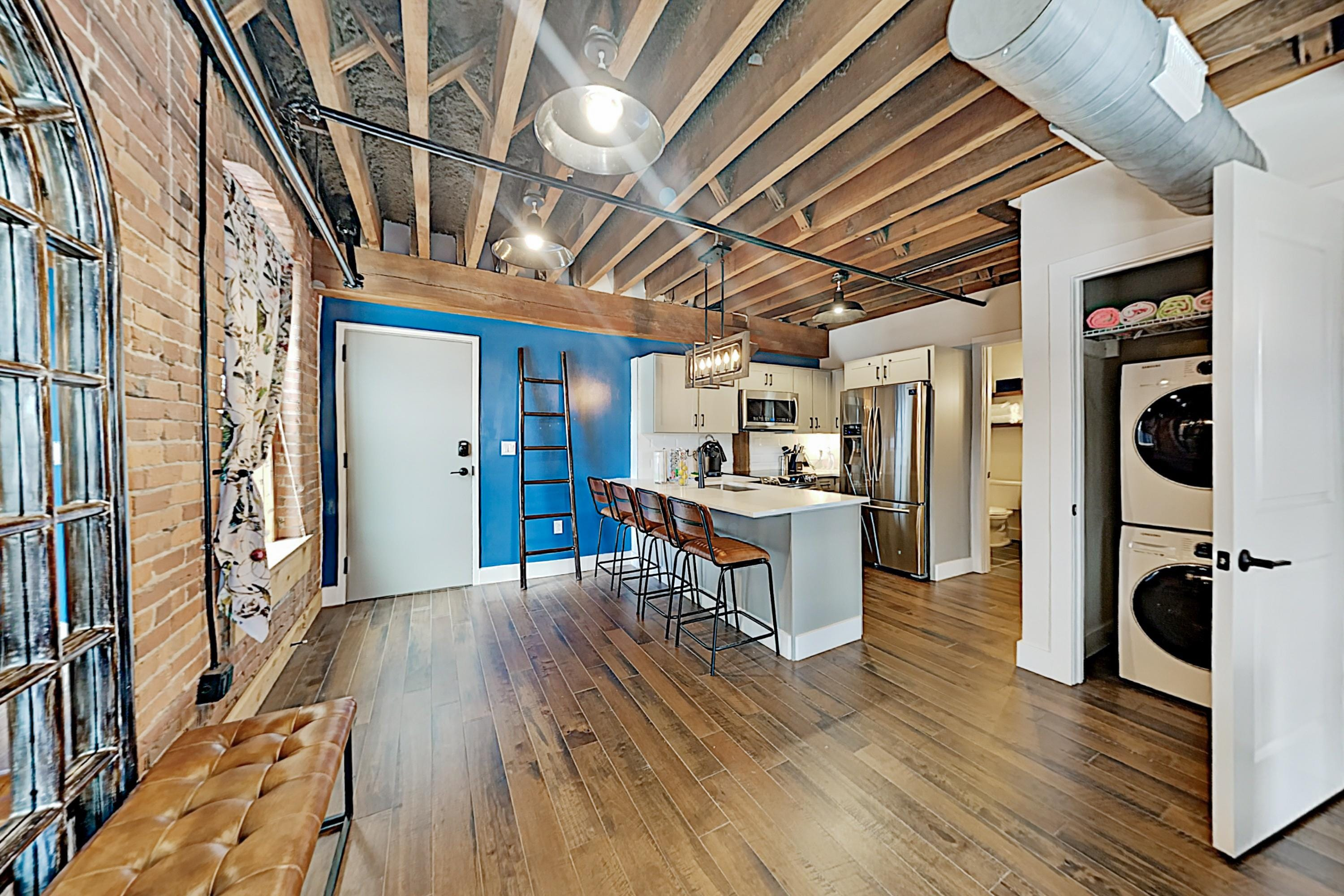 This updated property includes distinctive details like original graffiti on exposed brick, pipes, and beams.
