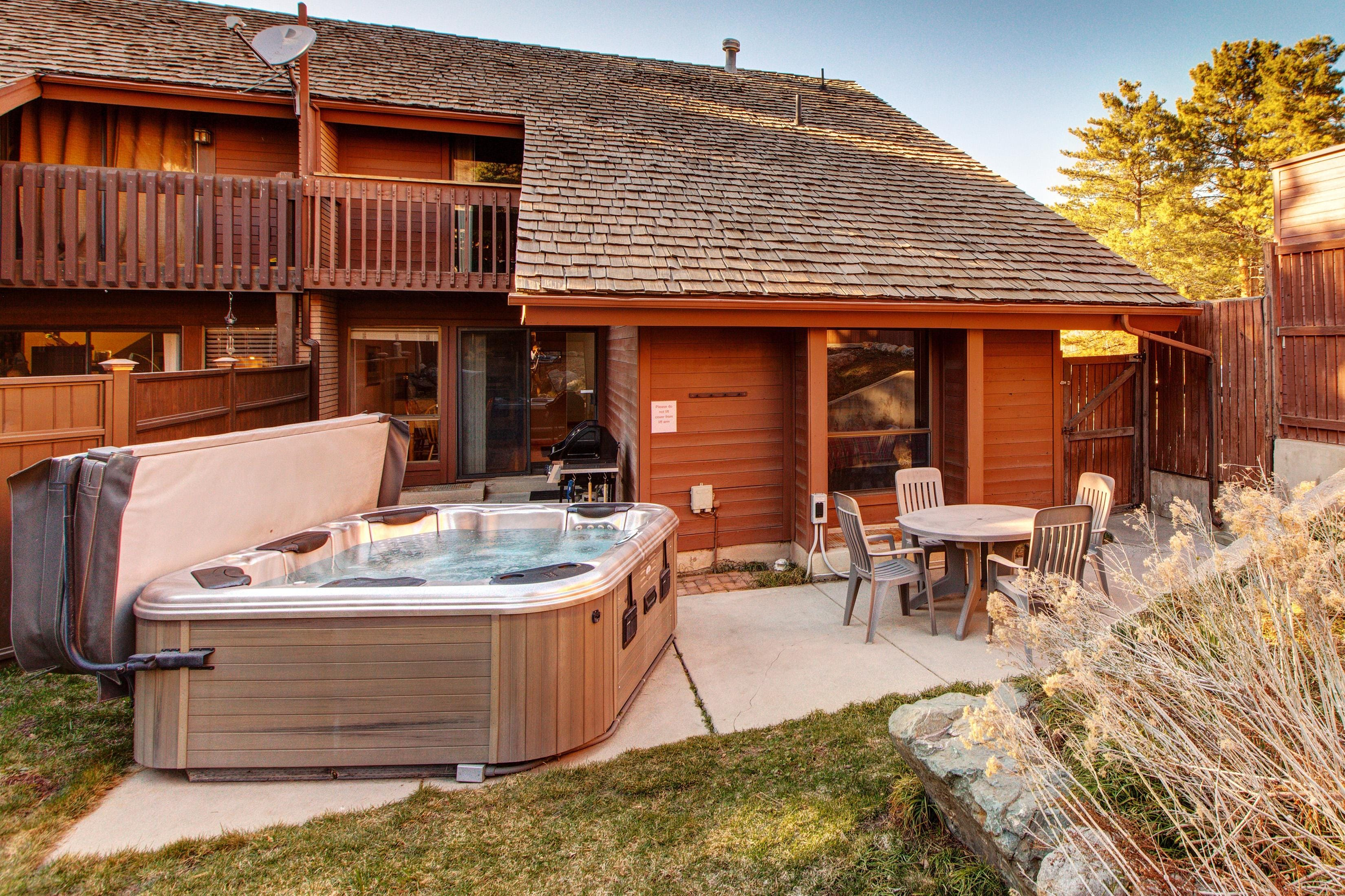 A private backyard includes a hot tub and a table with seating for 4.