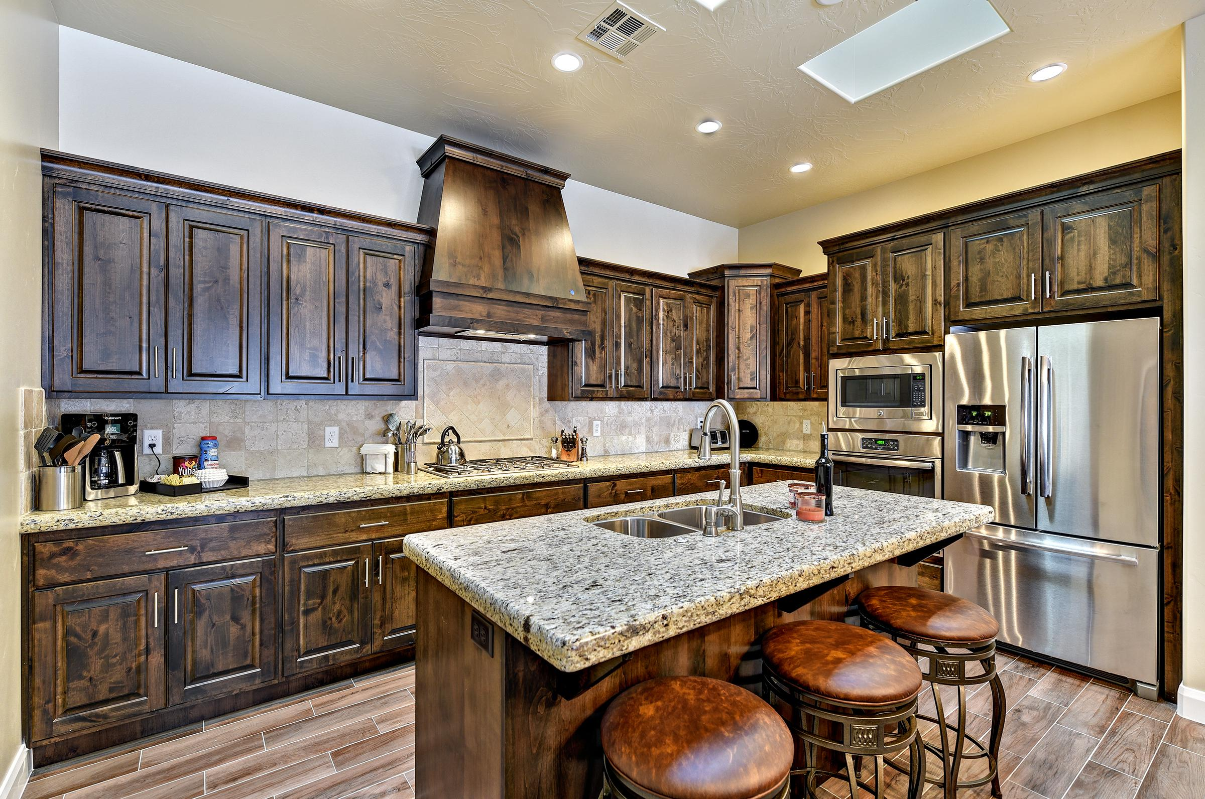 The Kitchen also includes a kitchen island and stainless steel appliances.