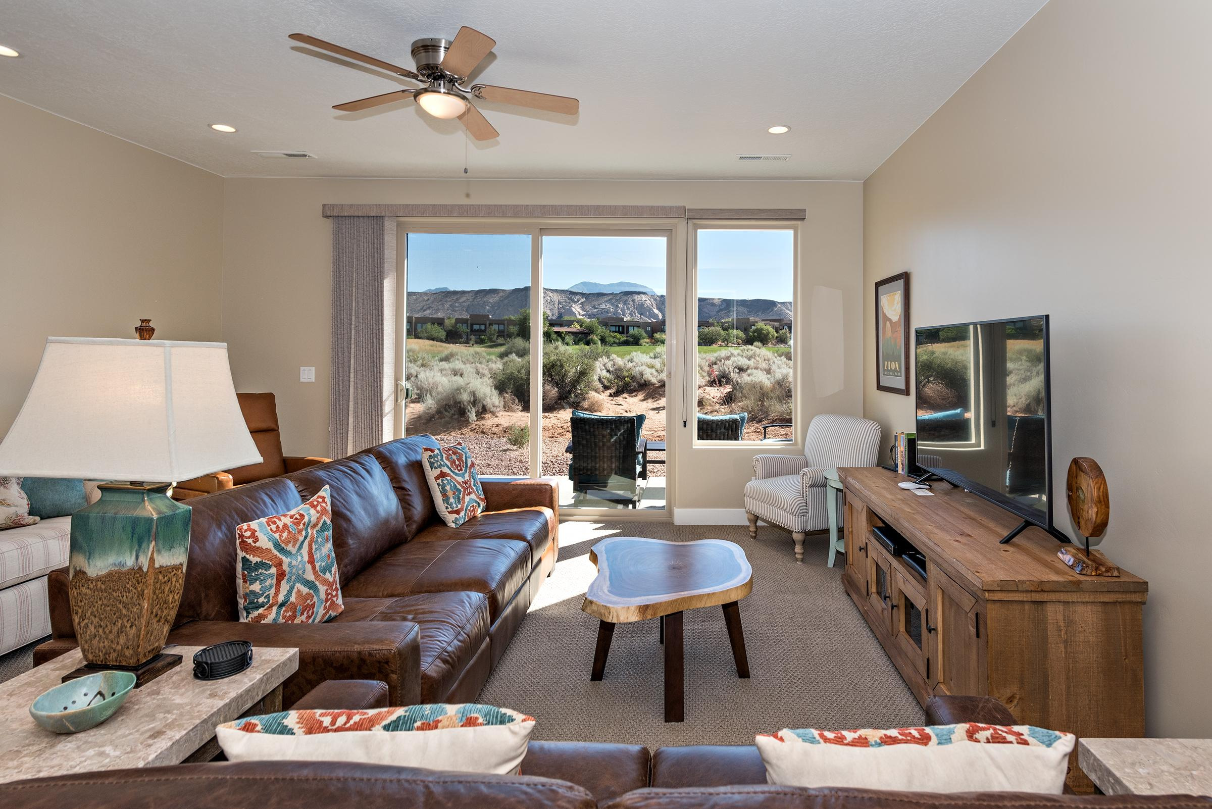 Spacious living room with sliding glass doors that open to patio facing the golf course.