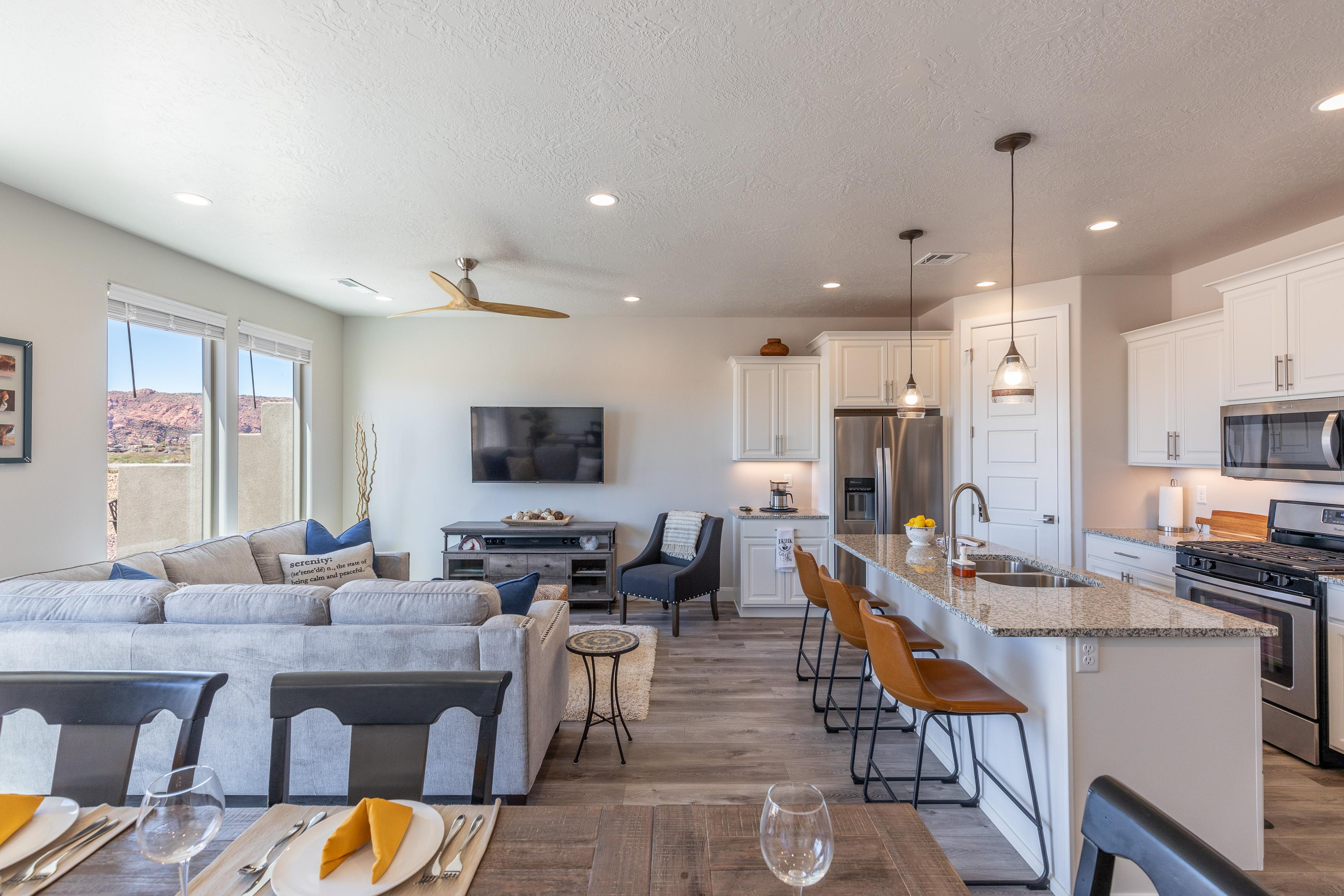 The living room is designed as an open floor plan and is a great gathering place for meals, games, or watching TV during your stay. Notice the view from this room!